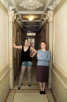 Mother and daughter standing in corridor