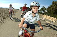 Children riding bicycles by beach