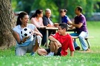 Hispanic mother with soccer ball talking to her son