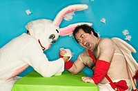 Cupid arm wrestling the Easter Bunny