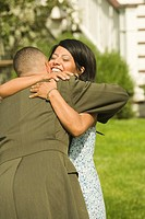 African military soldier hugging wife