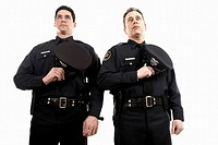 Male police officers holding their hats over their chest
