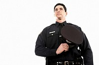 Male police officer holding his hat over his chest