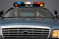 Male police officers riding in patrol car
