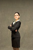 Hispanic businesswoman standing with arms crossed