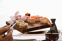 Woman´s hand holding tray of sushi