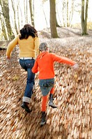 Mother and daughter running in woods