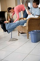 Woman mopping under husband's legs