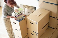 Woman packing books (thumbnail)