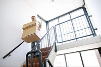 Man carrying stacked boxes down staircase (thumbnail)