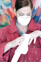 Woman wearing mask while wiping paint from hands