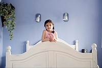 Young girl standing on bed