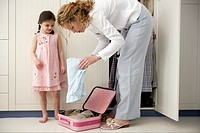 Mother and daughter packing suitcase