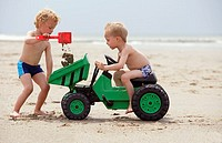 Young boys playing with toy digger on beach