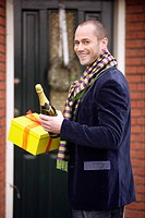 Man holding gifts and champagne