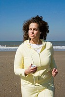 Woman listening to music, jogging on beach