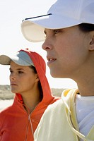 Side view of young women wearing baseball hats at beach