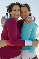 Two women hugging at beach (thumbnail)