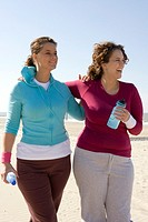 Two women walking arm in arm at beach