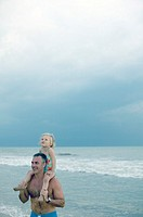 Man carrying daughter on beach