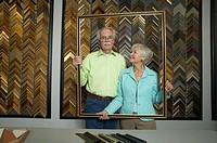 Senior couple holding frame in frame shop