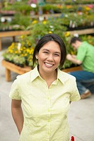 Asian woman smiling at plant nursery