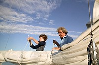 Father and son untying sail