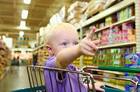 Toddler boy pointing at something in grocery store