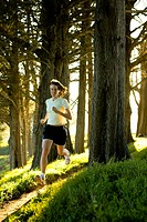 Woman jogging in forest at sunrise