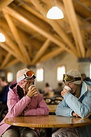 Young women in lodge drinking hot chocolate