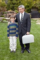 Businessman father and son standing in backyard