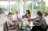 Businesspeople sitting at table with dog