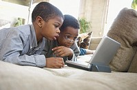 Two young boys watching DVD player