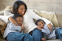 Mother playing with sons on couch
