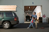 Father and son tying lumber down onto car