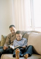 African father and son reading on sofa