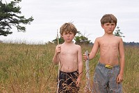 Two young boys standing in field