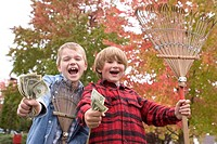 Two happy boys holding rakes and money