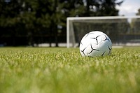 Soccer ball on grass near goal net