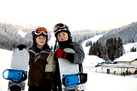Young boys holding snowboards on slopes, Cascade Mountains, Washington