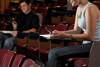 Students using cell phones in empty auditorium