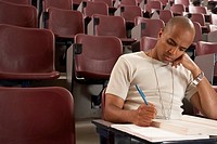 African male student taking notes in auditorium