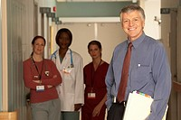 Male doctor standing in corridor with people in the background