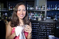 Hispanic woman wiping glass in bar