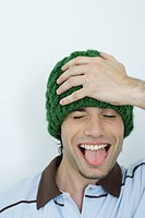 Young man wearing knit hat, hand on head, eyes closed, sticking out tongue, portrait