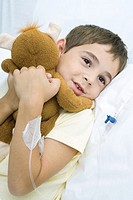 Boy lying in hospital bed with IV drip in arm, hugging stuffed animal