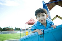 Boy on playground equipment, smiling at camera