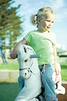 Girl on playground rocking horse, looking away