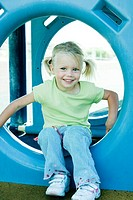 Girl sitting in playground equipment