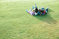 Children lying on grass, reading book together